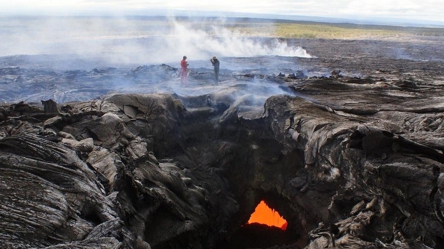 This Monday, Sept. 15, 2014, photo provided by the U.S. Geological Survey shows geologists from the Hawaiian Volcano Observatory surveying the lava flow from the June 27th flow from the Kilauea volcano in Pahoa, Hawaii. On Tuesday, Sept. 16, 2014, Hawaii County spokesman Kevin Dayton said the slow-moving lava is expected to bypass homes in the Kaohe Homesteads subdivision, and the lava is about 19 days from reaching Pahoa Village Road. (AP Photo/U.S. Geological Survey)