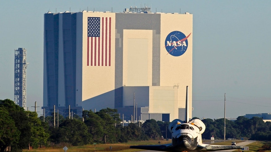 The space shuttle Atlantis leaves the Kennedy Space Center in Cape Canaveral, Florida November 2, 2012, heading towards its new home at the privately operated Kennedy Space Center Visitor Complex adjacent to the NASA spaceport. NASA's third and last surviving space shuttle moved to its retirement home on Friday after a 10-mile (16 km) road trip from the Kennedy Space Center in Florida. Atlantis, which ended the 30-year-old space shuttle program with a final flight last year, will be the star attraction of a new $100 million exhibit at the Kennedy Space Center Visitor Complex. REUTERS/Joe Skipper  (UNITED STATES - Tags: SCIENCE TECHNOLOGY) - RTR39WK9