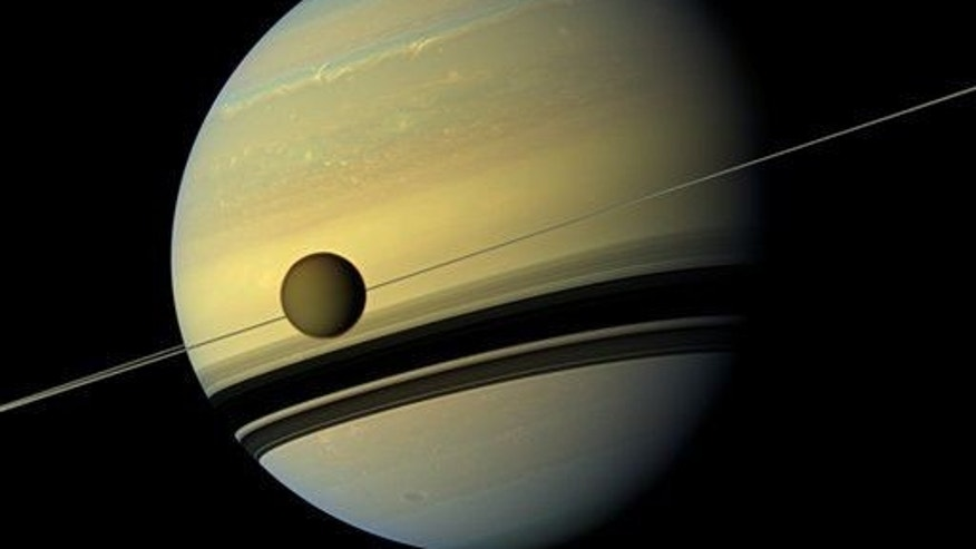 Saturn's largest moon Titan passes in front of the giant planet. The view of Saturn and one of its moons was made by Cassini's wide-angle camera on May 6, 2012.