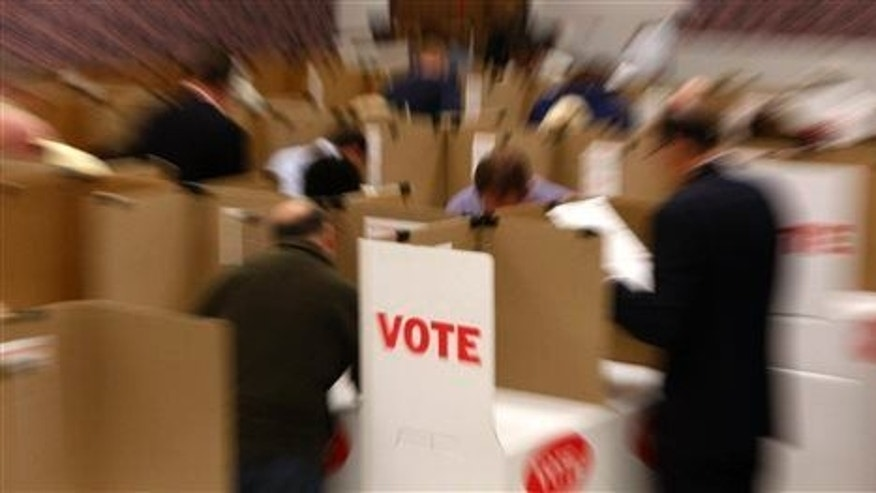 In this Friday, Oct. 29, 2010 file photo, voters in voting booths are blurred by the action of a zoom lens at the Oklahoma County Election Board during early voting in Oklahoma City.