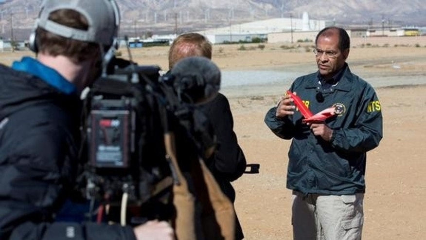 "Christopher Hart, acting chairman of the National Transportation Safety Board, uses a model to explain how SpaceShipTwo's ""feathering"" descent system works. The system deployed too early during the vehicle's tragic test flight of Oct. 31, 2014."