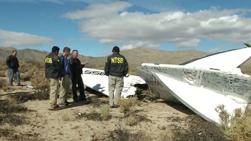 National Transportation Safety Board inspectors stand near debris from the tail section of Virgin Galactic's SpaceShipTwo, which crashed during a test flight on Oct. 31, 2014.