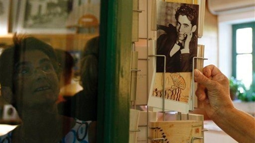 A woman looks at some postcards with the image of Federico Garcia Lorca.