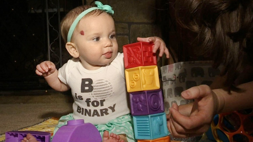 In this July 31, 2014 photo, 6-month-old Marilyn Mathews plays with blocks at home in Langhorne, Penn. She is wearing a shirt that reads, 'B is for Binary.'