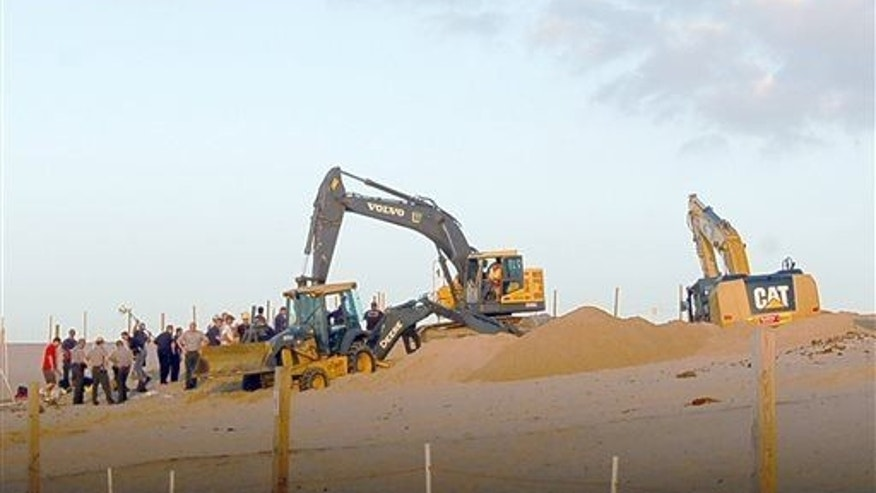 In this July 12, 2013, photo rescue workers with heavy equipment working to free 6-year-old Nathan Woessner who fell into a hole in a massive sand dune at the Indiana Dunes National Lakeshore.
