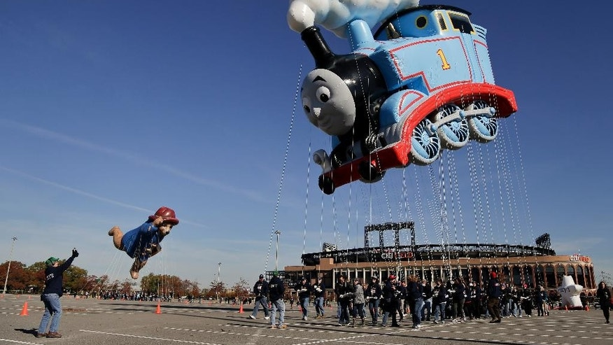 FILE - In this Nov. 8, 2014, file photo, handlers steer Thomas the Tank Engine and Paddington Bear balloons through the parking lot at CitiField in New York. The two balloons were taken for practice runs along with four other new character balloons in preparation for the 88th Annual Macy's Thanksgiving Day Parade. Thomas the Tank Engine will be the parade's largest balloon by helium volume and the one containing the most balloon fabric ever used on one character. (AP Photo/Julie Jacobson, File)
