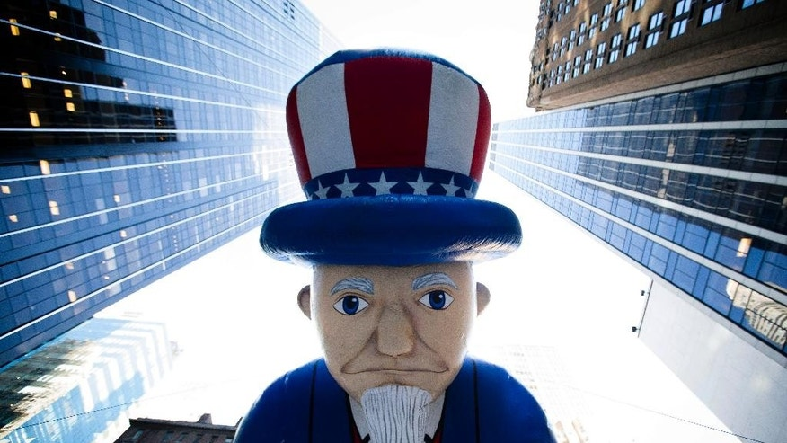 FILE - In this Nov. 28, 2013, file photo, a giant Uncle Sam balloon is marched down Sixth Avenue during the 87th Annual Macy's Thanksgiving Day Parade in New York. Helium makes the huge balloons in the parade sail high above the crowd. (AP Photo/John Minchillo, File)