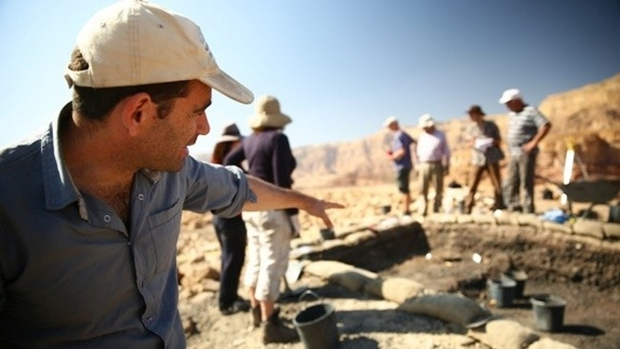 In this photo from 2013, archaeologist Erez Ben-Yosef points to a trench at Slaves' Hill, a copper smelting camp in Timna Valley.