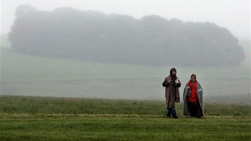People walk on the fields near Salisbury, the present-day site of a medieval city.