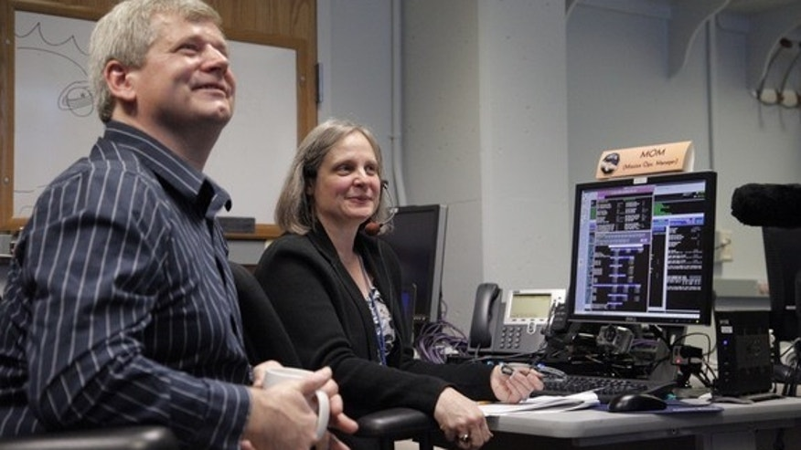 NASA's New Horizon Pluto flyby mission operations manager Alice Bowman and operations team Karl Whittenburg watch screens for signals confirming that the New Horizons probe awoke from hibernation on Dec. 6, 2014. The New Horizons mission is man