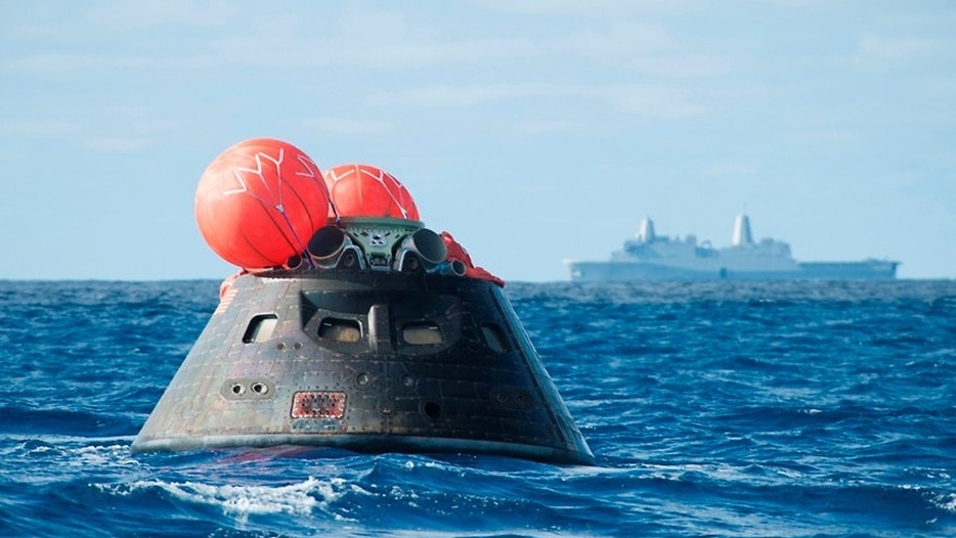 This Dec. 5, 2014 image provided by NASA shows NASA's Orion spacecraft after splash down as it awaits the U.S. Navy's USS Anchorage in the Pacific ocean.