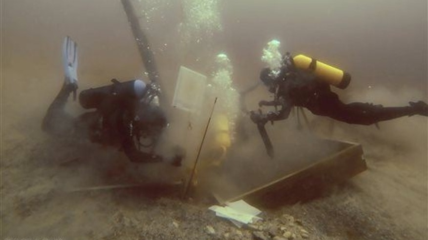 Divers inspect a hole being dug beside a wooden beam jutting from the floor of Lake Michigan during a search for the Griffin.
