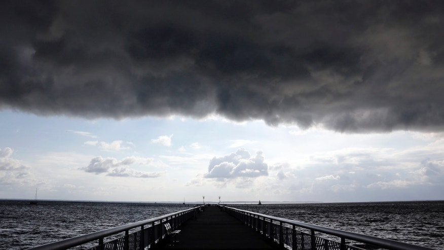 Dark clouds fill the Autumn sky over the jetty in Andernos, southwestern France, Nov. 4, 2014.