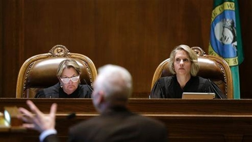 In this Sept. 3, 2014 file photo, Supreme Court Justices Susan Owens, left, and Debra Stephens listen to Thomas Ahearne, attorney for the coalition that sued the state over education funding, during a hearing before the state Supreme Court, in Olympia, Wash.