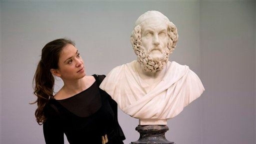 A Sotheby's auction house employee poses for photographs with the Francis Harwood marble bust of the ancient Greek poet Homer in London, Friday, Nov. 28, 2014.