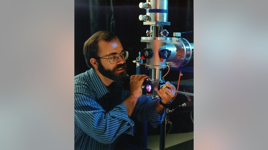Scott Sandford of NASA's Ames Research Center looks into the sample chamber of one of the cryovacuum systems to study the chemical processes that can happen in space.