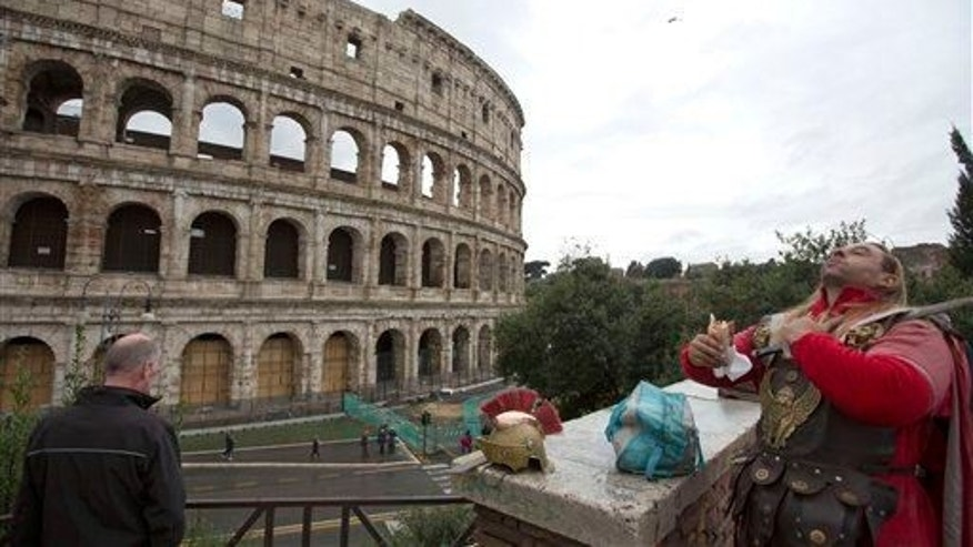 A man dressed as a gladiator enjoys his lunch in front of Rome's Colosseum, Friday Nov. 7, 2014.