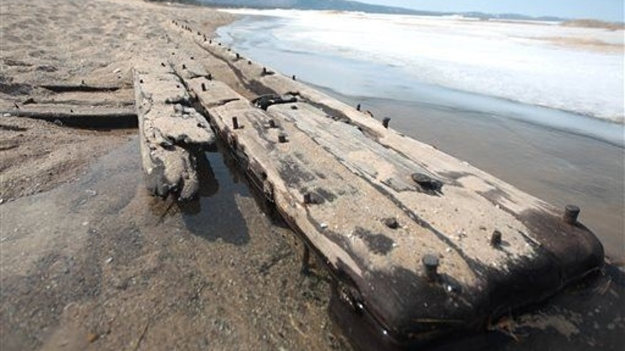 In this photo taken on April 6, 2014, the tip of a 40-foot-long section of a different shipwreck juts out of the sand along Lake Michigan.