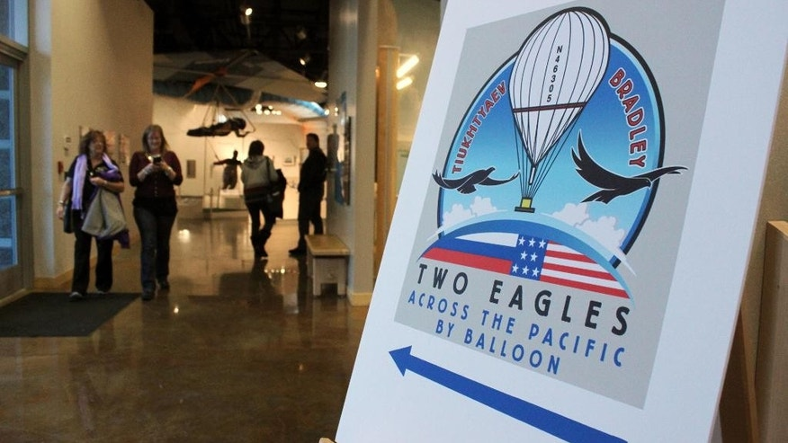 Visitors to the Anderson Abruzzo International Balloon Museum in Albuquerque, N.M., are directed to the mission control center for the Two Eagles Balloon flight on Friday, Jan. 30, 2015. The balloon has surpassed world records for distance and duration during its trip across the Pacific Ocean. It was scheduled to land on Mexico's Baja California peninsula on Saturday, Jan. 31, 2015. (AP Photo/Susan Montoya Bryan)