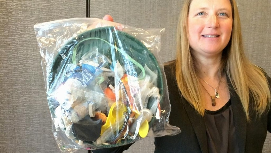 Jenna Jambeck, an environment engineering professor at the University of Georgia, holds a plastic baggie with trash collected last fall from a clean up at Panama Beach, Fla., Thursday, Feb. 12, 2015, at the AAAS (American Association for the Advancement of Science) conference in San Jose, Calif. Each year about 8.8 million tons of plastic ends up in the world oceans, a quantity much higher than previous estimates, according to a new study that tracked marine debris from its source. (AP Photo/Seth Borenstein)