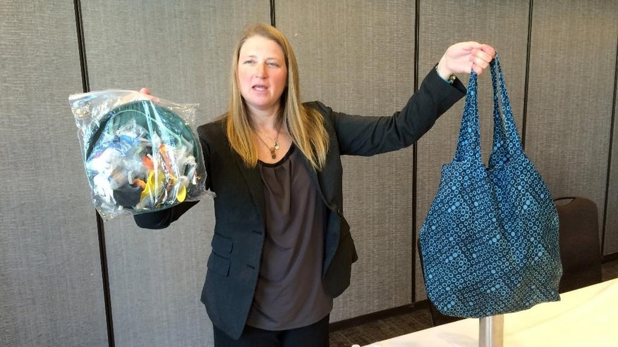 Jenna Jambeck, an environment engineering professor at the University of Georgia, holds a shopping bag filled with plastic trash from the ocean, right, and a plastic baggie with trash collected last fall from a clean up at Panama Beach, Fla., Thursday, Feb. 12, 2015, at the AAAS (American Association for the Advancement of Science) conference in San Jose, Calif. Each year about 8.8 million tons of plastic ends up in the world oceans, a quantity much higher than previous estimates, according to a new study that tracked marine debris from its source. (AP Photo/Seth Borenstein)
