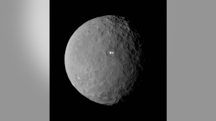 This Feb. 19, 2015 image shows the swarf planet Ceres provided by NASA, taken by the agency's Dawn spacecraft from a distance of nearly 29,000 miles. It shows that the brightest spot on Ceres has a dimmer companion, which apparently lies in the same basin, seen at center of the image. Dawn is preparing to rendezvous with the largest object in the asteroid belt located between Mars and Jupiter, scheduled to go into orbit Friday, March 7 after a three-year journey. Dawn is about 590 miles in diameter. (AP Photo/NASA/JPL-Caltech/UCLA/MPS/DLR/IDA)
