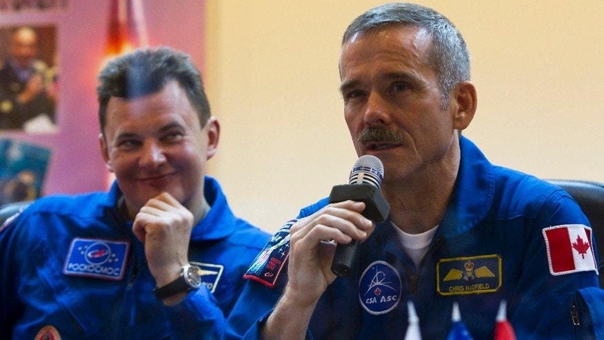 File photo. Canadian astronaut Chris Hadfield (R) attends a news conference behind a glass wall at the Baikonur cosmodrome Dec. 18, 2012.
