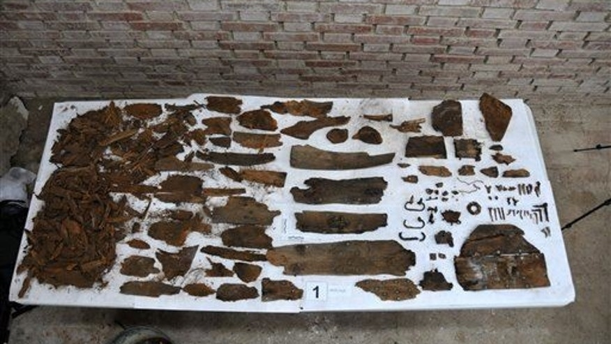 "This photo taken on Saturday, Jan. 24, 2015 and provided by Aranzadi Science Society, shows the initials ""M.C"" on a plank, right, and remains of a coffin."