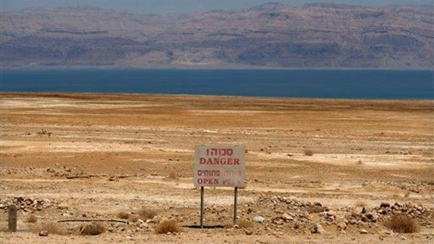 In this photo taken Thursday, May 28, 2009, a warning sign is seen near the Dead Sea coast.