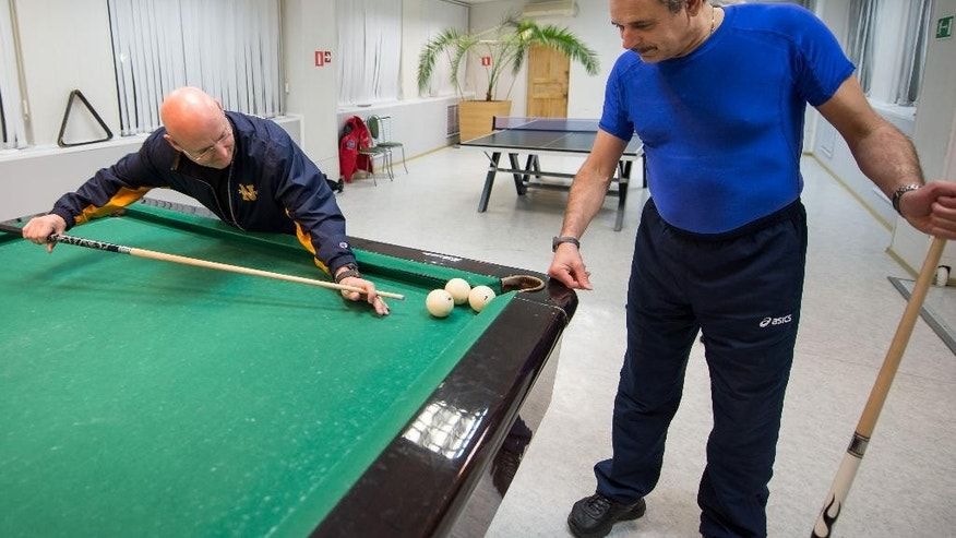 In this Thursday, March 19, 2015 photo provided by NASA, astronaut Scott Kelly, left, plays pool with Russian cosmonaut Mikhail Kornienko, of the Russian Federal Space Agency (Roscosmos), at the Cosmonaut Hotel in Baikonur, Kazakhstan. On Saturday, March 28, 2015, Kelly and Kornienko will travel to the International Space Station to begin a year-long mission living in orbit. (AP Photo/NASA, Bill Ingalls)