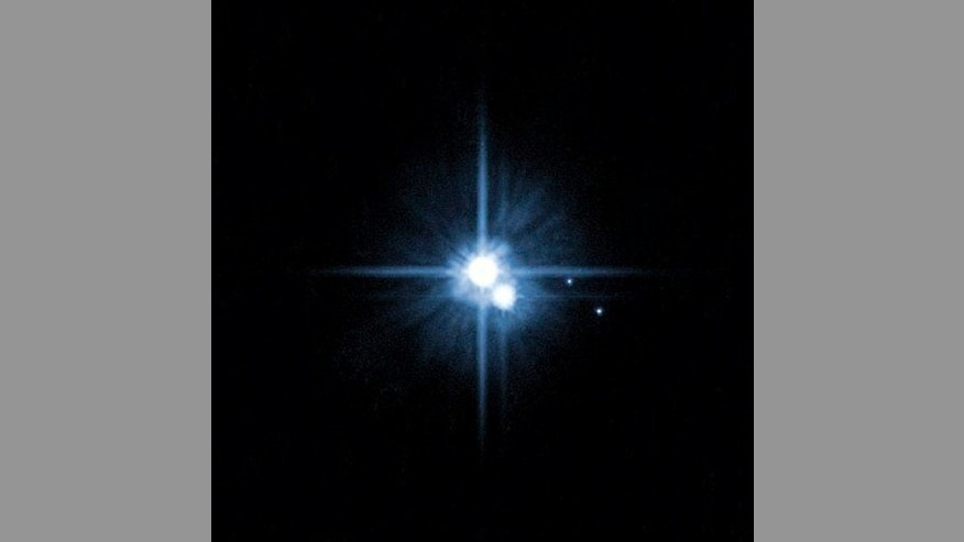 This file image provided by NASA on Feb. 22, 2006, from its Hubble Space Telescope shows Pluto and three of its five moons.