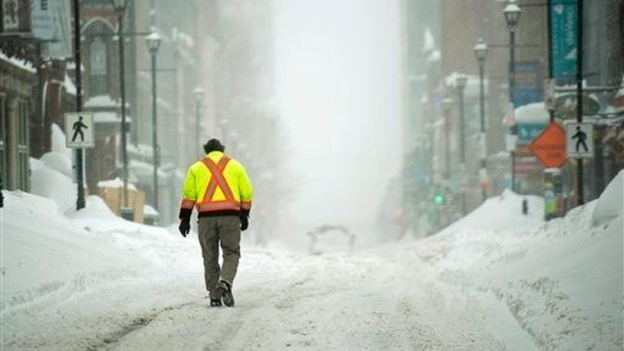 A pedestrian walks on a downtown street in Halifax, Canada on Wednesday, March 18, 2015.