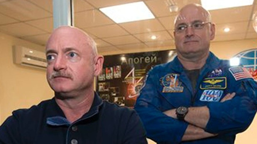 U.S. astronaut Scott Kelly, right, crew member of the mission to the International Space Station, ISS, poses through a safety glass with his brother, Mark Kelly, also an astronaut after a news conference in the Russian leased Baikonur cosmodrome, Kazakhstan, Thursday, March 26, 2015.
