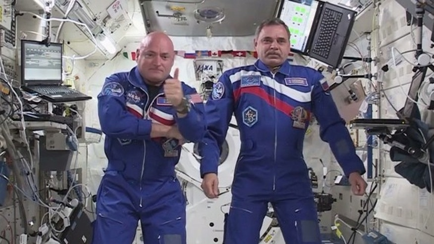 NASA astronaut Scott Kelly (left) gives a thumb's up sign while floating next to fellow one-year crewmate Mikhail Kornienko of Russia on the International Space Station after a video chat with NASA chief Charles Bolden and others on March 30, 2