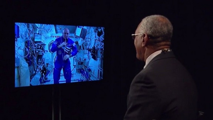 NASA Administrator Charles Bolden (right) speaks to one-year astronaut Scott Kelly on the International Space Station via a video link on March 30, 2015.