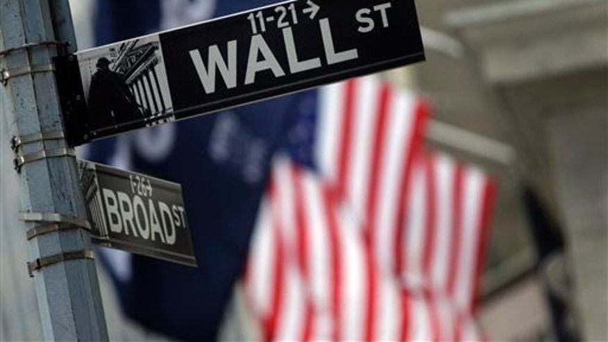 This Oct. 2, 2014, file photo shows a Wall Street sign adjacent to the New York Stock Exchange, in New York.