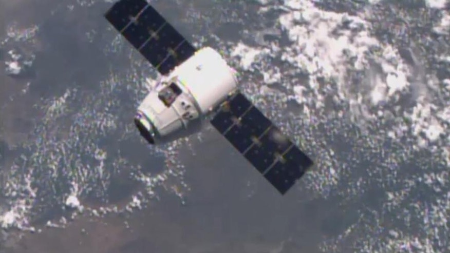 In this image from NASA-TV shows the SpaceX Dragon-6 resupply capsule Friday April 17, 2015 as it holds 30 meters from the International Space Station as they cross over the coast of Namibia. (NASA-TV via AP)