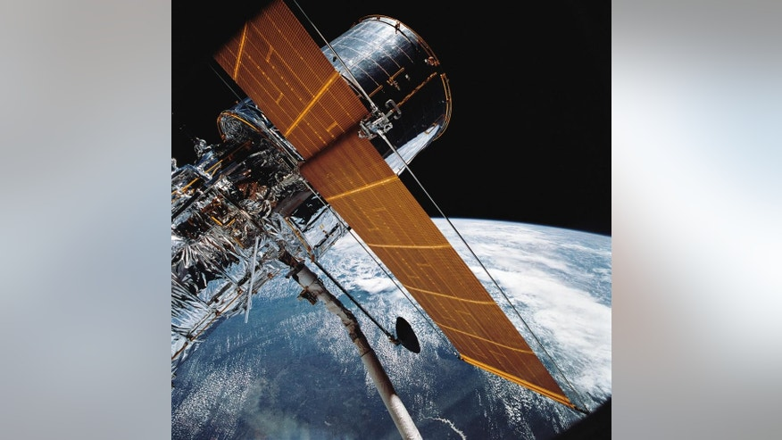In this April 25, 1990 photograph provided by NASA, most of the giant Hubble Space Telescope can be seen as it is suspended in space by Discovery's Remote Manipulator System (RMS) following the deployment of part of its solar panels and antennae. This was among the first photos NASA released on April 30 from the five-day STS-31 mission.  The Hubble Space Telescope, one of NASA'S crowning glories, marks its 25th anniversary on Friday, April 24, 2015. With more than 1 million observations, including those of the farthest and oldest galaxies ever beholden by humanity, no man-made satellite has touched as many minds or hearts as Hubble.  (NASA via AP)