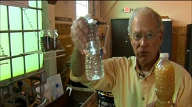 Water Missions International co-founder and CEO George Greene holds samples of water taken after and before the purification process.