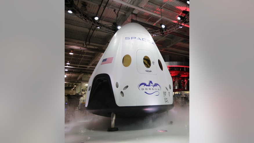 FILE - In this May 29, 2014, file photo, the SpaceX Dragon V2 spaceship is unveiled at its headquarters in Hawthorne, Calif. SpaceX is scheduled to conduct the first major test of its brand new, super-streamlined launch escape system for astronauts, Wednesday, May 6, 2015. (AP Photo/Jae C. Hong, File)