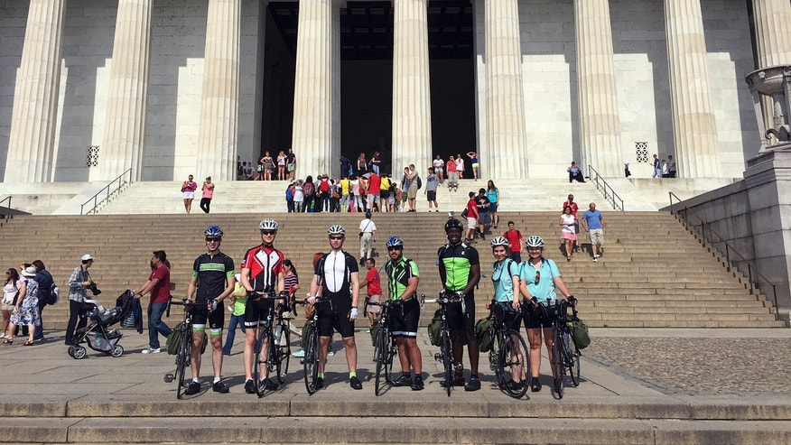 In this June 1, 2015 photo provided by Drew Bent, seven students from Harvard and MIT pose with their bicycles at the Lincoln Memorial in Washington.