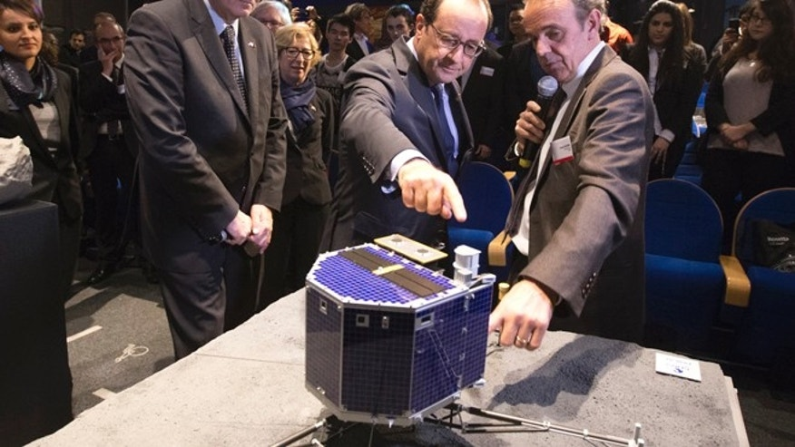 Nov. 12, 2014: In this file photo, French President Francois Hollande, center, with French astrophysicist Francis Rocard look at a model of Rosetta lander Philae, as they visit the Cite des Sciences at La Villette in Paris during a broadcast of the Rosetta mission as it orbits around comet 67/P Churyumov-Gersimenko.