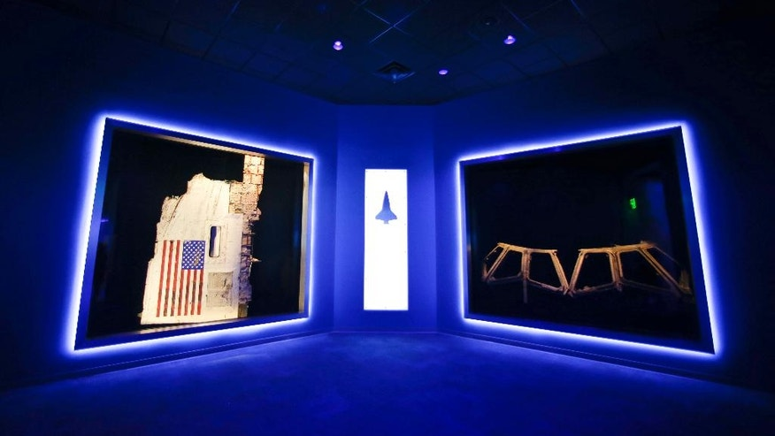This Tuesday, July 21, 2015 photo shows a side body panel of space shuttle Challenger, left, and the cockpit widows of Columbia, right, displayed at the Forever Remembered exhibit and memorial for the astronauts that perished on the two shuttles at the Kennedy Space Center Visitor Complex, in Cape Canaveral, Fla. (AP Photo/John Raoux)