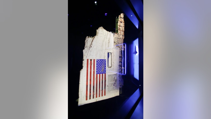 "In this Tuesday, July 21, 2015 photo, the left side body panel of space shuttle Challenger is displayed in a glass case at  the ""Forever Remembered"" exhibit at the Kennedy Space Center Visitor Complex in Cape Canaveral, Fla. Challenger's wreckage _ all 118 tons of it, salvaged from the Atlantic _ was buried in a pair of former missile silos, 90 feet deep. The chamber containing this particular fuselage section had never been opened _ until the exhibit began to take shape. (AP Photo/John Raoux)"