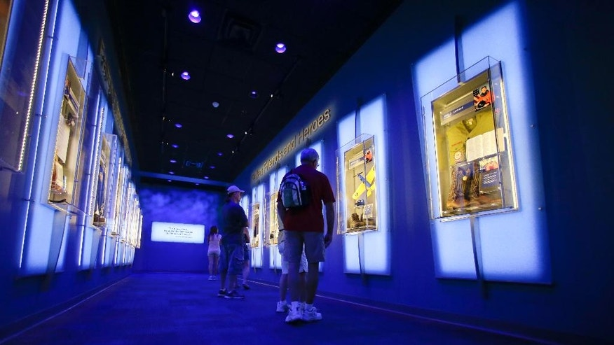 "In this Tuesday, July 21, 2015 photo, visitors look over display cases at the ""Forever Remembered"" exhibit and memorial for the astronauts that perished on the Columbia and Challenger space shuttles, at the Kennedy Space Center Visitor Complex in Cape Canaveral, Fla. NASA's intent is to show how the astronauts lived, rather than how they died. (AP Photo/John Raoux)"