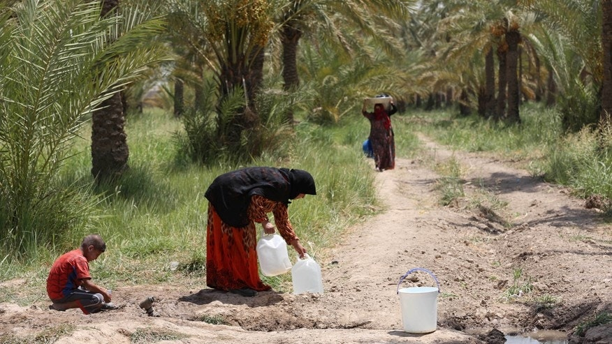 Iraqis displaced by conflict collect water at al-Takia refugee camp in Baghdad, Iraq, Thursday, July 30, 2015.