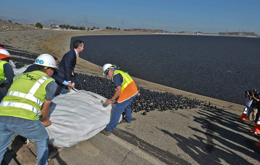 Los Angeles City Councilman Mitch Englander, Mayor Eric Garcetti (wearing a yellow tie) and LADWP workers deposit the final installment of 96 million shade balls into the Los Angeles Reservoir. (Art Mochizuki, LADWP)