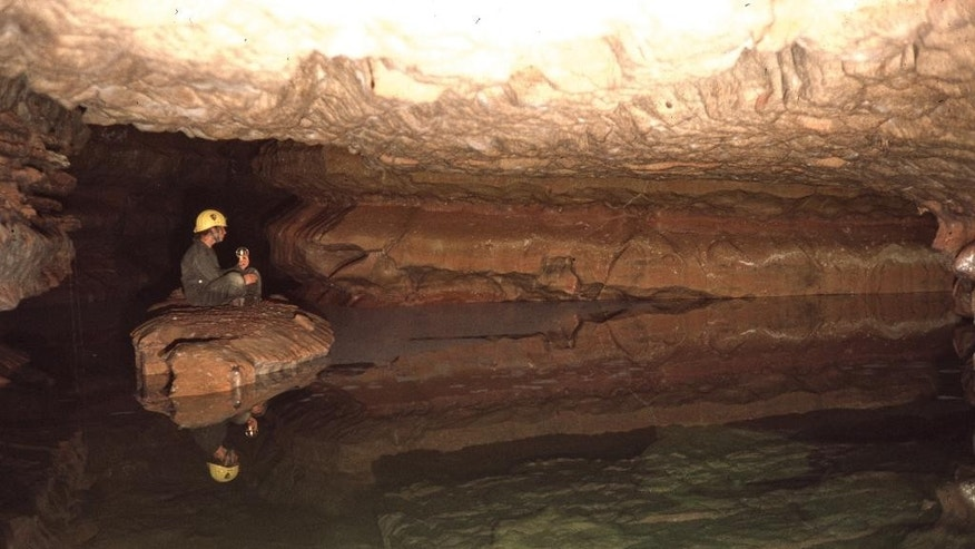 This 1982 photo provided by The National Park Service shows a park employee sitting on a rock in Calcite Lake at The Wind Cave National Park in the Black Hills of South Dakota. The underground lakes, which were discovered in the 1960s, aren't home to any animal life but prominent cave microbiologist Hazel Barton has discovered there is bacteria - albeit scant - in the lakes. Barton hopes to decipher how the bacteria survives and answer questions about how it interacted before multicellular organisms came along and perhaps find new sources of antibiotics. (The National Park Service via AP)