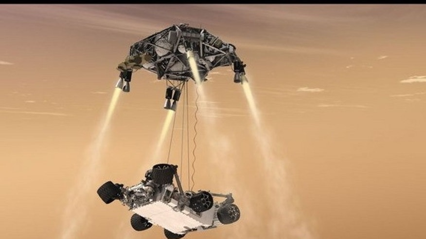"This artist's concept shows the sky-crane maneuver during the descent of NASA's Curiosity rover to the Martian surface, which engineers dubbed ""seven minutes of terror."" The Mars 2020 mission will leverage the design of this landing system and"