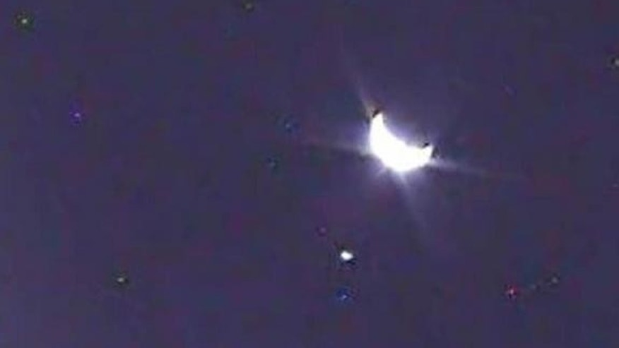 An image of Earth, taken by NASA's LCROSS satellite, shows the planet in its crescent phase. The smaller light to the left is the moon.